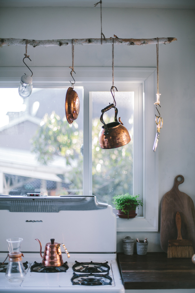 Before and After: A Modern Rustic Kitchen Makeover - Copper pots on a DIY branch hanger
